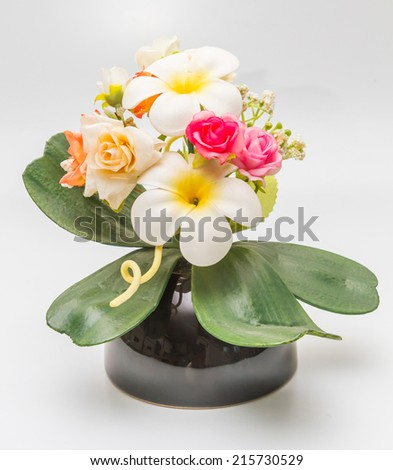 Fake flower, Colorful decoration artificial flower with plumeria and rose in vase on white background. - stock photo