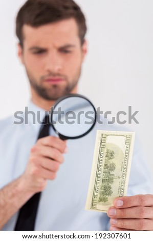 Fake or real? Concentrated young man in shirt and tie looking through a magnifying glass at the paper currency while standing isolated on white background  - stock photo