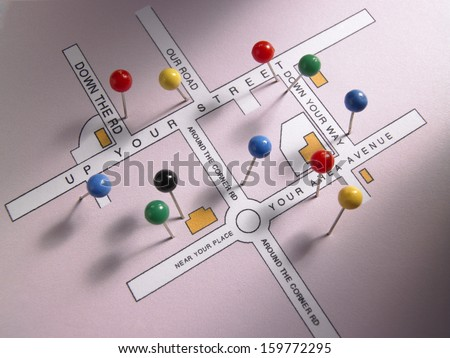 Fake pink 'Up Your Street' road map with drawing pins - stock photo