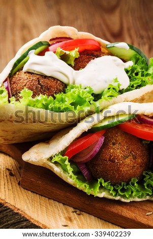 Falafel and fresh vegetables in pita bread on wooden table - stock photo
