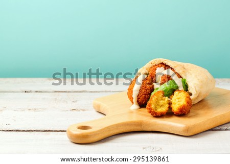 Falafel balls in pita with tahini sauce on wooden board - stock photo