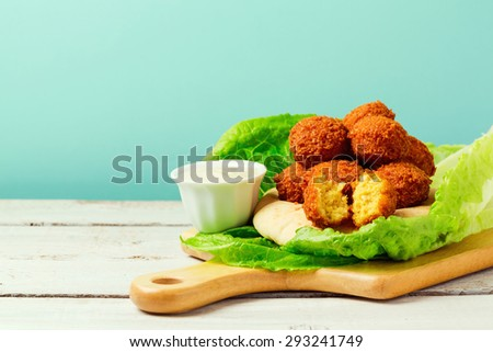 Falafel balls served with pita and tahini sauce on a wooden board - stock photo