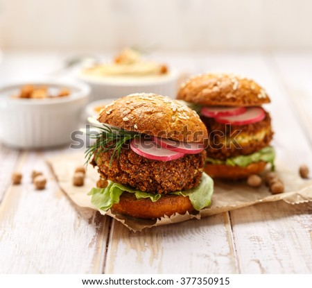 Falafel burger with addition of fresh  radish, onion, dill and Iceberg lettuce on a wooden rustic table. Healthy and delicious  vegetarian dish - stock photo