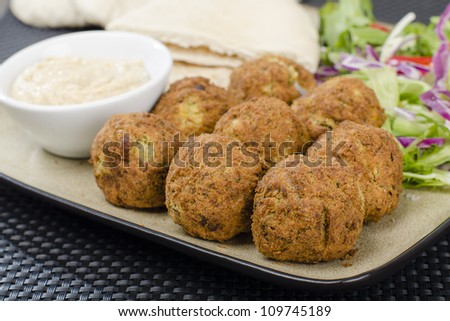 Falafel - Deep fried chickpeas balls served with tahini, salad and pitta bread. - stock photo