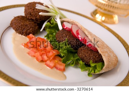 falafel in pita bread dressed on a gold lined plate with tomatoes and lettuce with a garnish - stock photo