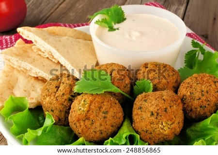 Falafel on lettuce with pita bread and tzatziki sauce close-up