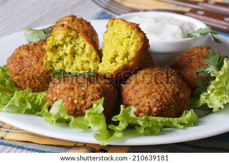 Falafel on the lettuce with tzatziki sauce close-up on the table. horizontal  - stock photo