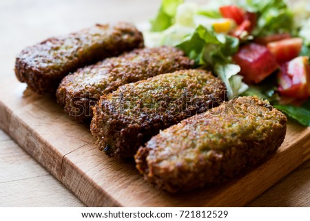 Falafel with Salad on wooden surface.