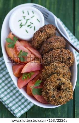 Falafel with tomatoes and sauce on green table - stock photo