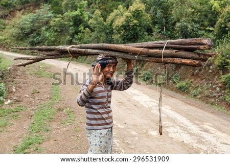 FALAM, MYANMAR - JUNE 17 2015: Local woman carries wood on her head in the recently opened to foreigners area of Chin State - western Myanmar (Burma) - stock photo