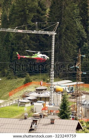 Falcade, Belluno, Italy - August 21, 2015: Cement mixer truck works at building site under construction the new modern cabin lift in the  ski area San Pellegrino - stock photo