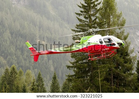 Falcade, Belluno, Italy - August 21, 2015: transport helicopter provides material for a construction site in the mountains