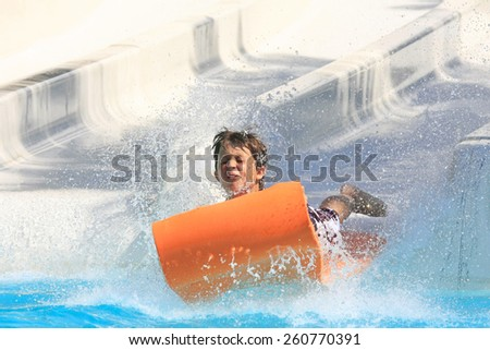 Faliraki,Rhodes,Greece-August,20,2015:One young boy on the mat racer slide in Water park,Mat racer slide is very popular for young people in the Water Park - stock photo