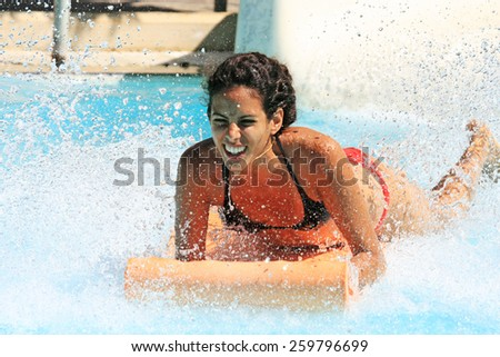 Faliraki,Rhodes,Greece-August,24,2015:Young happy girl gets into pool after landing on the mat racer slide.Mat racer slide is very popular for young people in the Water Park. - stock photo