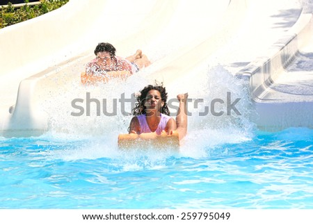 Faliraki,Rhodes,Greek-August,12,2015:Two young girls on the mat racer slide in Water park,Mat racer slide is very popular for young people in the Water Park - stock photo
