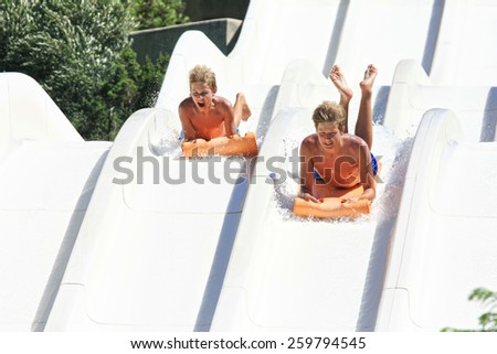 Faliraki,Rhodes,Greek-August,17,2015:Two young men on the mat racer slide in Water park,Mat racer slide is very popular for young people in the Water Park ; - stock photo