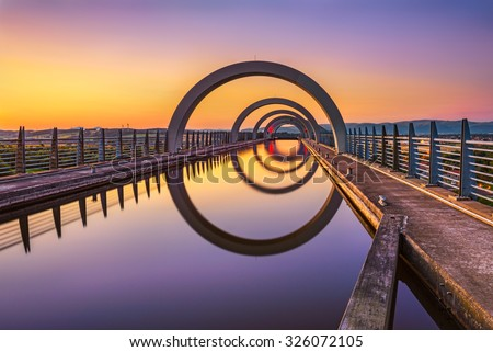 Falkirk Wheel at sunset. Falkirk Wheel is a rotating boat lift in Scotland and connects the Forth and Clyde Canal with the Union Canal. Long exposure. - stock photo