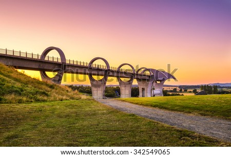 Falkirk Wheel at sunset. Falkirk Wheel is a rotating boat lift in Scotland and connects the Forth and Clyde Canal with the Union Canal. - stock photo