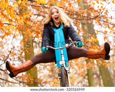 Fall active lifestyle concept. Happy crazy woman girl vivid color shawl relaxing in autumn park riding bicycle with her legs in the air having fun - stock photo