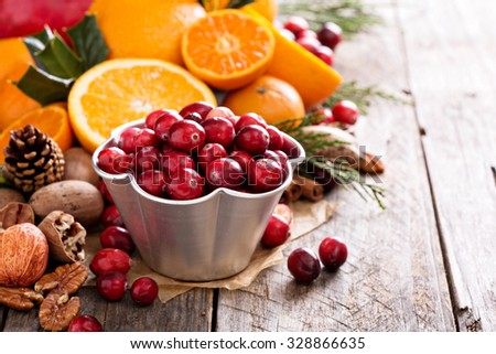 Fall and winter ingredients still life with oranges, cranberry, nuts and spices - stock photo