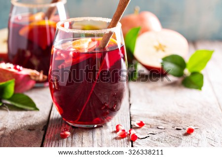 Fall and winter sangria with apples, oranges, pomegranate and cinnamon - stock photo
