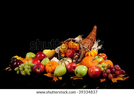 fall arrangement of fruits and vegetables in a cornucopia on a black background - stock photo