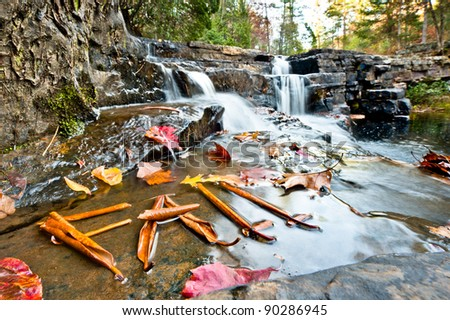Fall at Dismal Falls. Leaves in front of a waterfall spelling FALL. - stock photo
