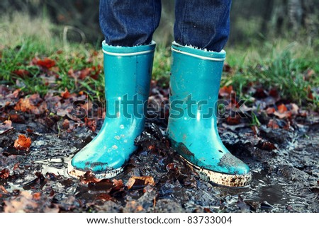 Fall / Autumn concept - Rain boots in mud puddle. Blue woman rain boots outdoors in action. - stock photo