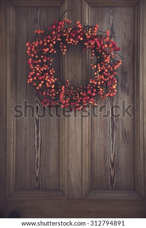Fall berry wreath hanging on a wooden door - stock photo