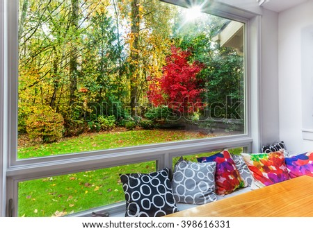 Fall color and leaves on the grass from large picture window - stock photo