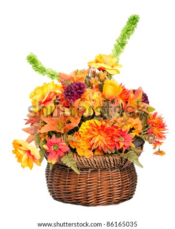 Fall color silk flower arrangement in basket isolated on white - stock photo