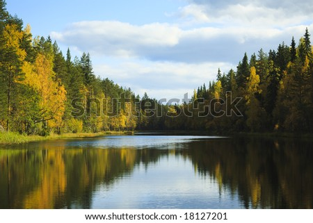 Fall colored forest reflections on the blue water