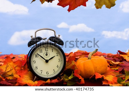Fall colored leaves with a black clock on a sky background, Fall Leaves - stock photo