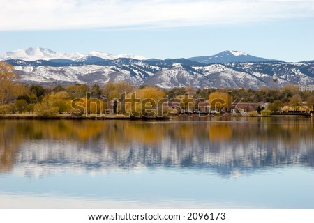 Fall colors against the snow capped mountains and reflection of both in the lake in the foreground.  Focus is on horizon line. - stock photo