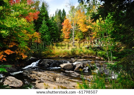 Fall colors and stream with metal bridge - stock photo