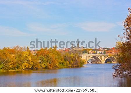 Fall colors of Potomac riverside and Key Bridge, Washington DC. A view on Georgetown University across Potomac River in autumn.  - stock photo