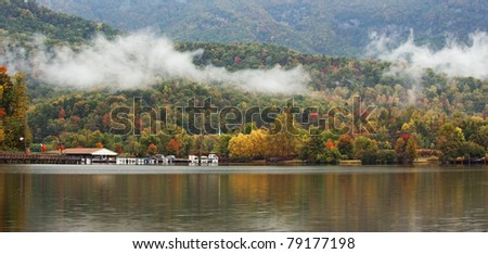 Fall colors of the trees reflecting in the water of a small lake in the mountains of North Carolina, USA. - stock photo