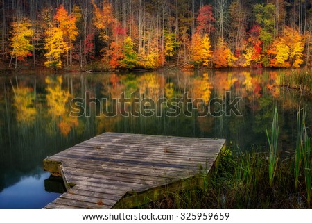 Fall colors reflect on the calm waters of Cranks Creek Lake in Southeastern Kentucky. - stock photo