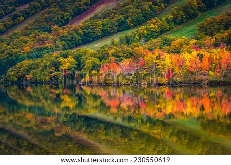 Fall colors reflecting in Echo Lake, in Franconia Notch State Park, New Hampshire. - stock photo