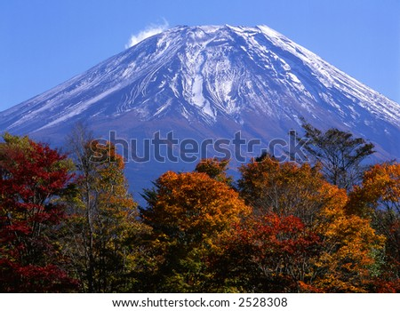 Fall colors with majestic Mount Fuji towering in the background. - stock photo
