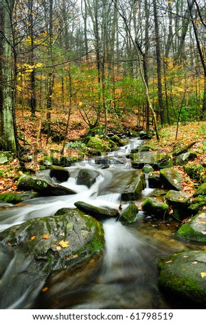 Fall colors with slow moving stream with boulders - stock photo