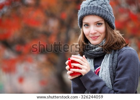 Fall concept - autumn woman drinking coffee on park bench under fall foliage. Beautiful young modern woman smiling happy and cheerful - stock photo