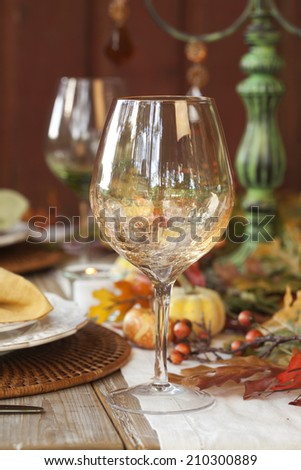 Fall dining table setting on rustic wood with focus on wine glass - stock photo