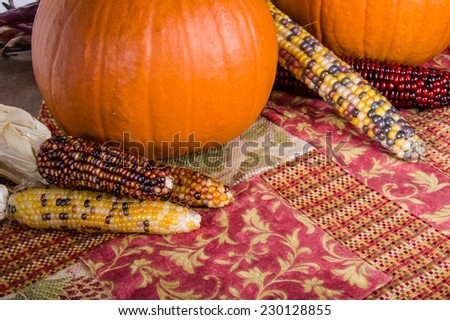 Fall display of harvested orange pumpkins and Indian Corn - stock photo