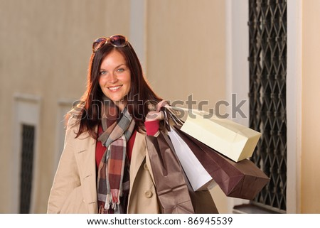Fall elegant woman carrying shopping bags posing city street sunset - stock photo