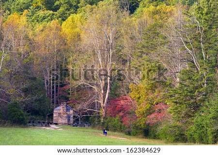 Fall foliage and an old cabin on display on Cade's Cove Loop Road  in  Great Smoky Mountains National Park, TN - stock photo