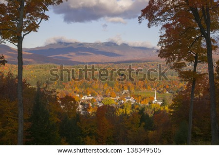 Fall foliage landscape overlooking Stowe Community Church and Stowe Village in the foreground, Stowe, Vermont, USA - stock photo