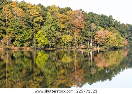 Fall foliage reflected on lake - stock photo