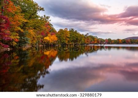 Fall foliage reflects in Hessian Lake at sunset, near Bear Mountain, NY - stock photo