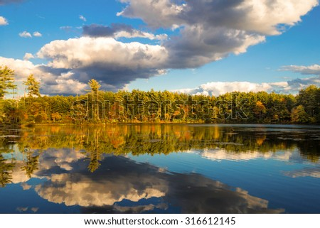 fall foliage with dramatic clouds and reflection in water - stock photo